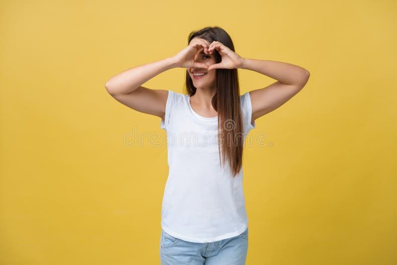 Здоровые глаза и зрение Портрет красивой счастливой женщины держа руки сердца форменные близко наблюдает усмехаться девушки крупн стоковое фото