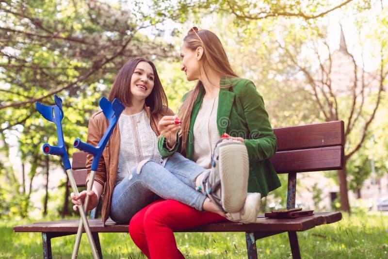 Здоровые женщина и друг с временем траты сломанной ноги совместно стоковые фотографии rf