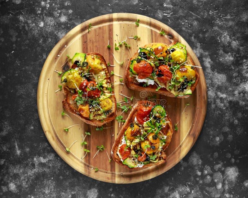 Здоровые здравицы с испеченными томатами сладостной вишни и зажаренными лентами zucchinin заморосили с бальзамическим уксусом стоковое изображение rf
