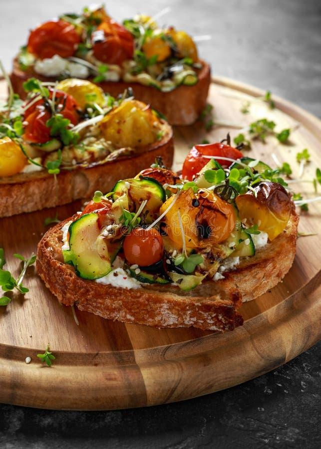 Здоровые здравицы с испеченными томатами сладостной вишни и зажаренными лентами zucchinin заморосили с бальзамическим уксусом стоковые изображения