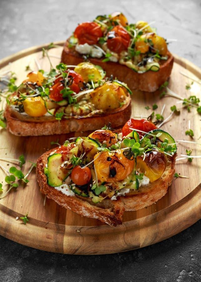 Здоровые здравицы с испеченными томатами сладостной вишни и зажаренными лентами zucchinin заморосили с бальзамическим уксусом стоковые фото