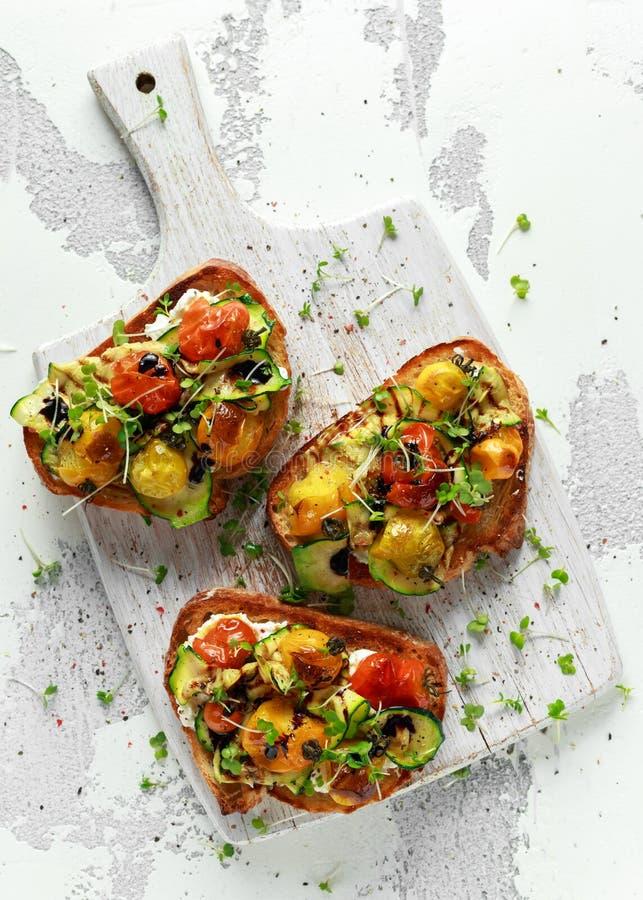 Здоровые здравицы с испеченными томатами сладостной вишни и зажаренными лентами zucchinin заморосили с бальзамическим уксусом стоковая фотография rf