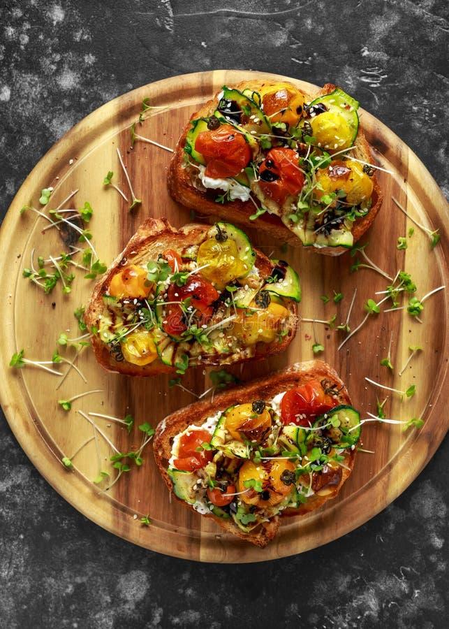 Здоровые здравицы с испеченными томатами сладостной вишни и зажаренными лентами zucchinin заморосили с бальзамическим уксусом стоковое фото