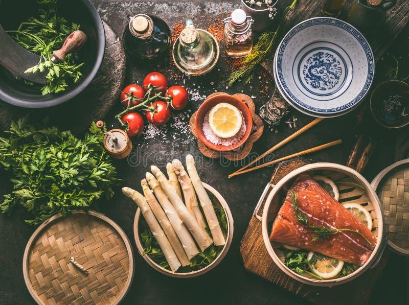 Здоровые ингредиенты для низкий варить еды карбюратора: семги в азиатском бамбуковом распаровщике, пуке спаржи, свежих травах и м стоковое фото