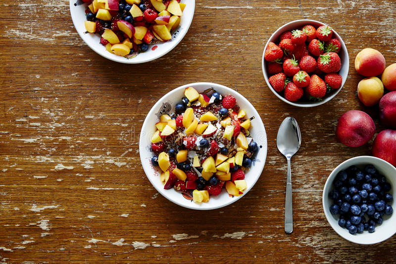 Здоровые органические свежие хлопья для завтрака с сезонными плодоовощами на винтажной таблице стоковые фото