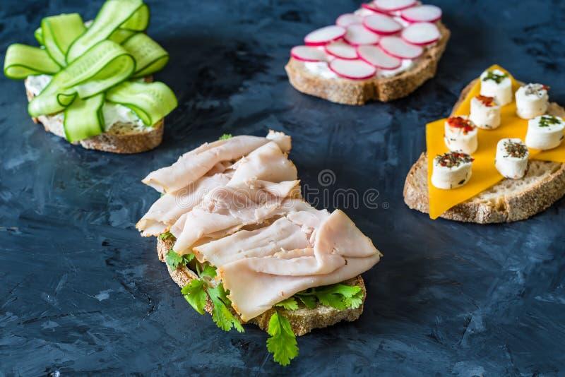 Здоровые открытые сэндвичи с овощами, морковами, редиской, сыром чеддера и пастромой индюка, огурцом на деревянной предпосылке стоковое фото rf