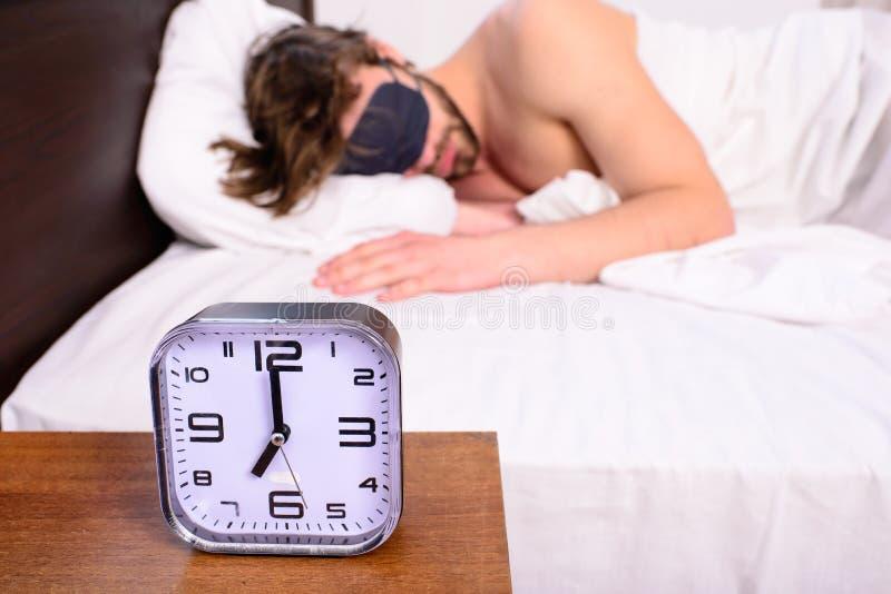 Здоровые подсказки сна Будильник перед звенеть Человек в сне маски глаза лучше Гай предпочитает ослабляет в темноте Большой колок стоковые фото