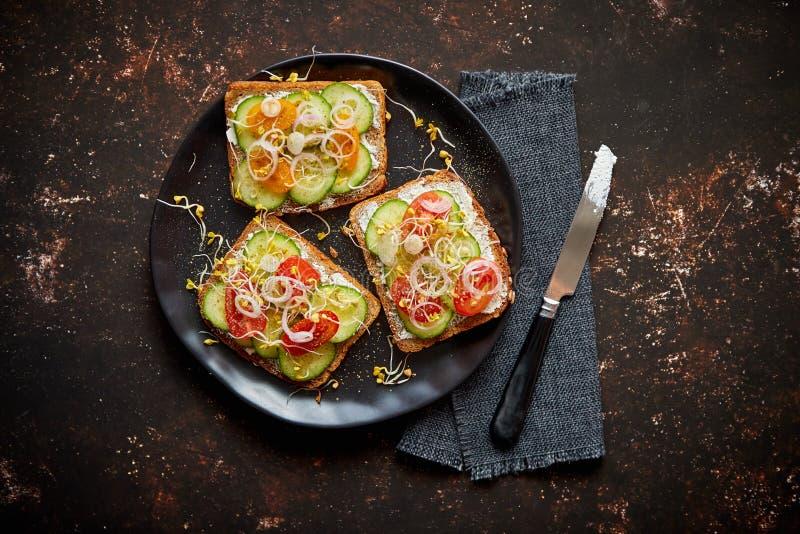 Здоровые тосты с cucomber, томатами и крошенными фета и ростками редиски стоковые фото