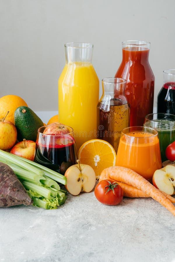 Здоровые фруктовые соки овоща и или smoothie в стеклянных бутылках, зрелых кусках апельсина, яблока, красного томата, моркови, се стоковые изображения