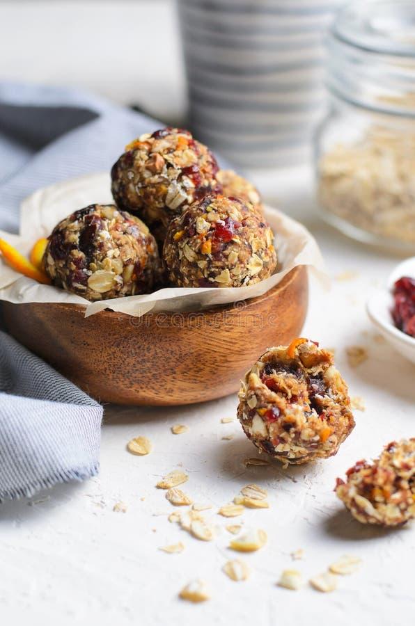 Здоровые шарики энергии, сырцовые шарики Vegan с овсяной кашей, клюква, даты и гайки стоковые фотографии rf