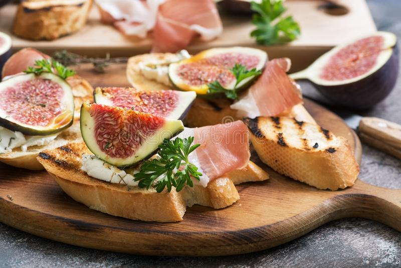 Здоровые bruschettas с плавленым сыром хлеба, ветчиной, смоквами и петрушкой на деревенской предпосылке Селективный фокус стоковое фото