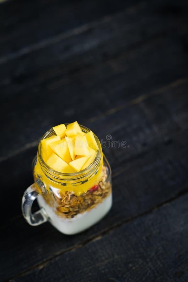 Здоровые muesli и йогурт завтрака с smoothie манго в стеклянных опарниках каменщика стоковые фотографии rf