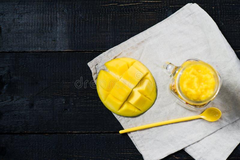 Здоровые muesli и йогурт завтрака с smoothie манго в стеклянных опарниках каменщика стоковые изображения