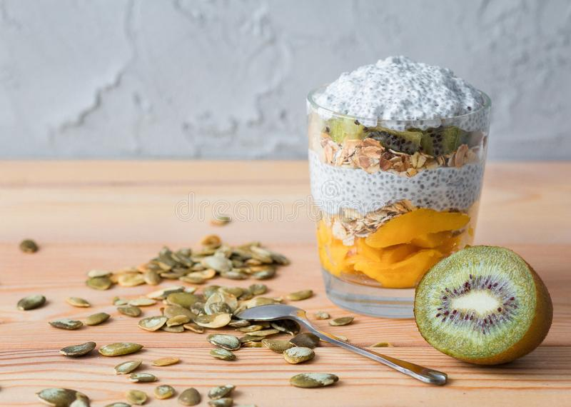 Здоровый ванильный пудинг chia в стекле с granola, манго и кивиом стоковые фотографии rf