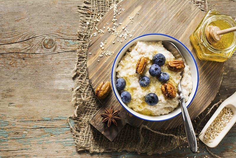 Здоровый завтрак: надоите кашу от отрубей овса на сниманный - надоите с медом, сочными голубиками, пеканами на простое деревянном стоковые фото