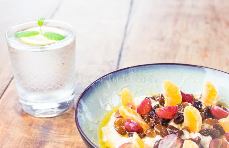 Здоровый завтрак - овсяная каша с вкусными плодом и стеклом воды с лимоном стоковые изображения