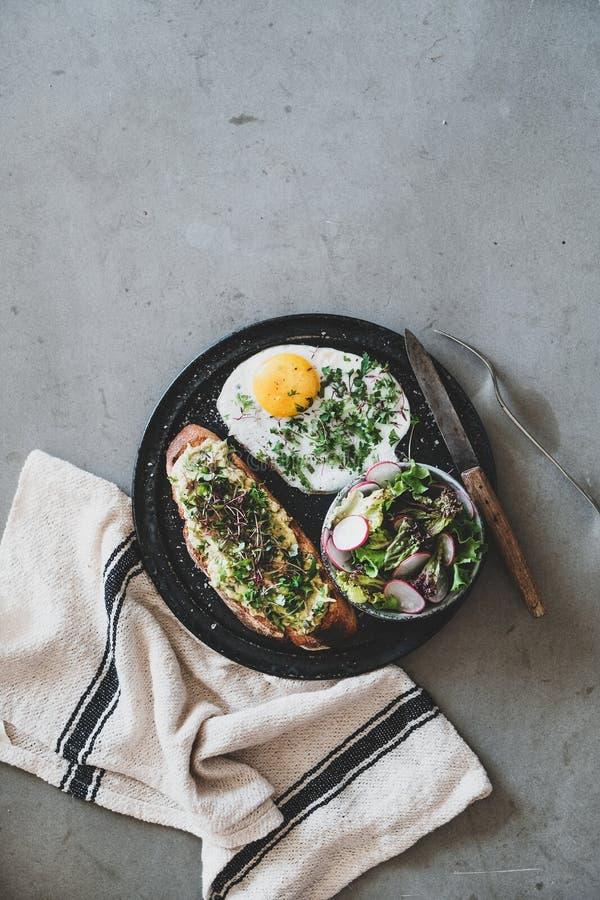 Здоровый завтрак с тостом авокадо, жаренным яйцом и салатом стоковые фото