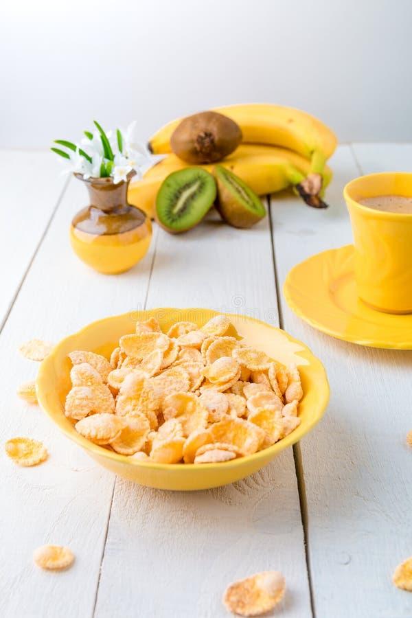 Здоровый завтрак с хлопьями хлопьев и плодоовощ около вазы с стоковая фотография