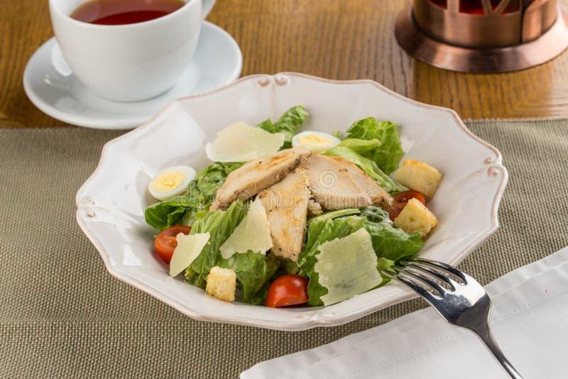 Здоровый зажаренный салат цезаря цыпленка с сыром пармезан и гренками на деревянном столе стоковое фото rf