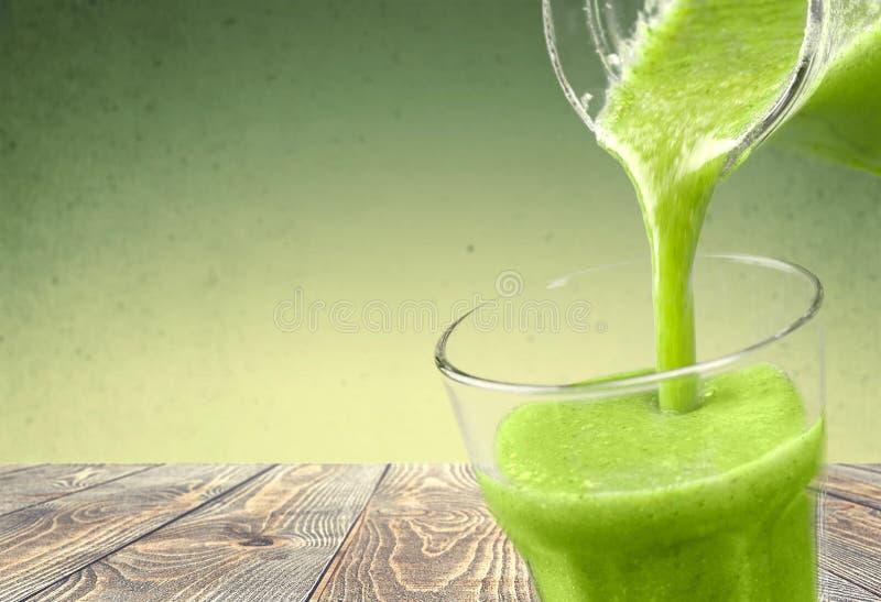 Здоровый зеленый smoothie лить в стекле стоковая фотография