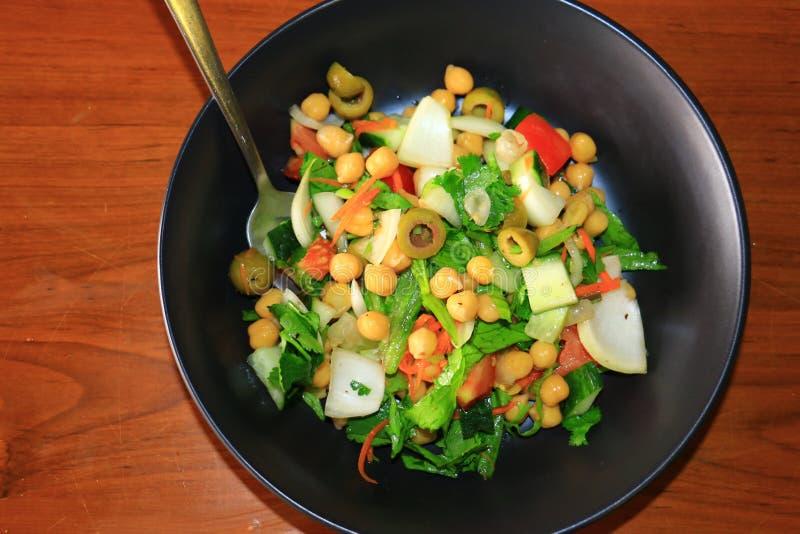 Здоровый и очень вкусный салат нута с оливками, огурцом, морковью, луком и салатом служил в черной плите стоковое изображение rf