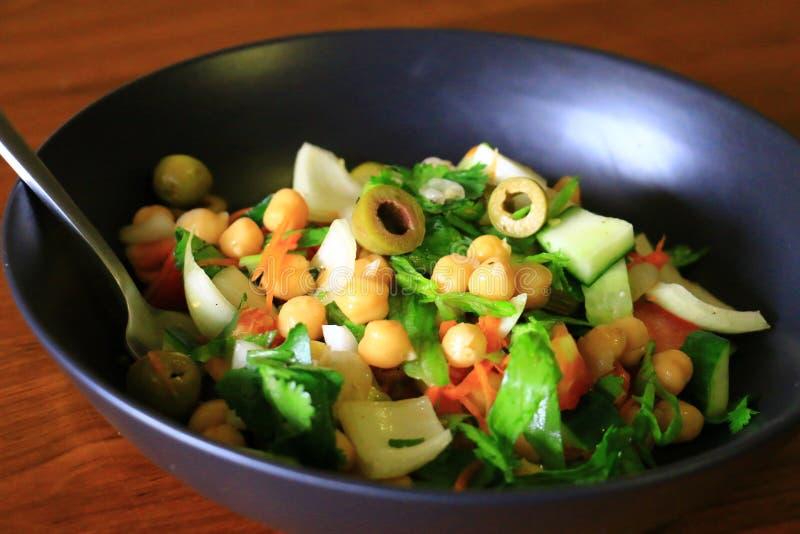Здоровый и очень вкусный салат нута с оливками, огурцом, морковью, луком и салатом служил в черной плите стоковое фото