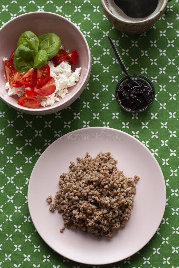 Здоровый и питательный завтрак: богатая плита гречихи, творога и салата с базиликом, небольшого шара томата чернослива стоковое фото