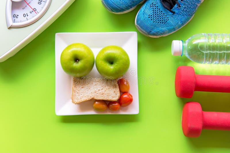 Здоровый образ жизни для диеты женщин с оборудованием спорта, тапками, весом масштаба, свежей водой Зеленые яблоки и хлеб стоковое изображение