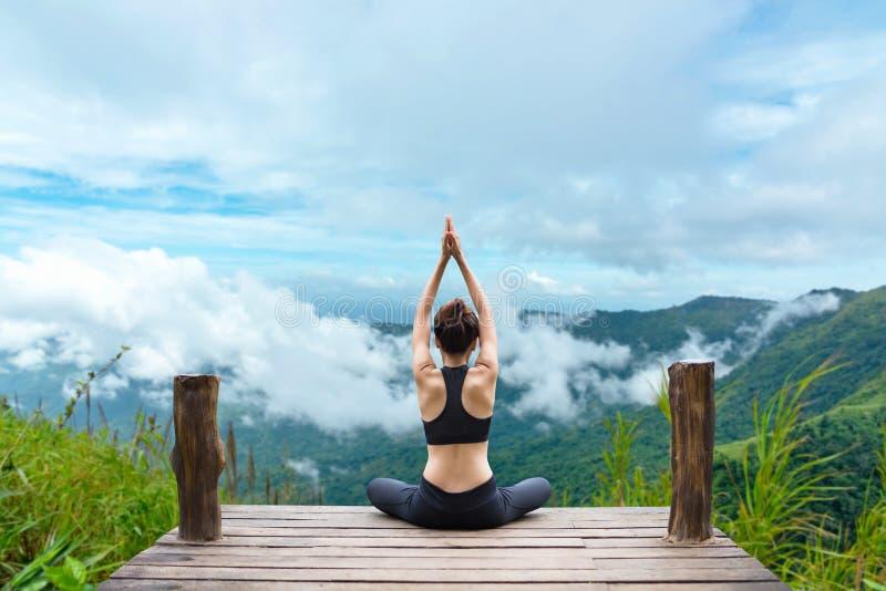 Здоровый образ жизни женщины сбалансировал практиковать размышляет и йогу энергии дзэна на мосте в утре природа горы стоковые изображения rf
