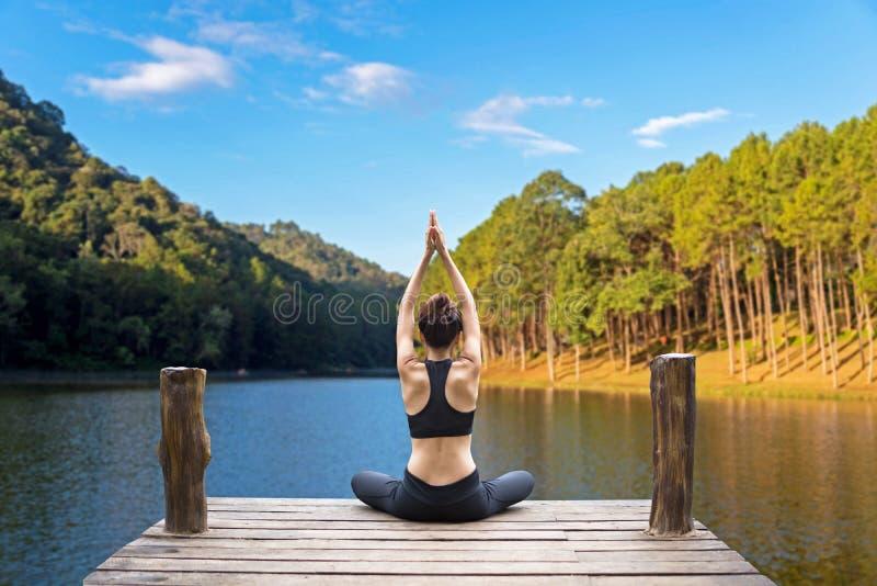 Здоровый образ жизни женщины сбалансировал практиковать размышляет и йогу энергии дзэна на мосте в утре природа стоковая фотография rf