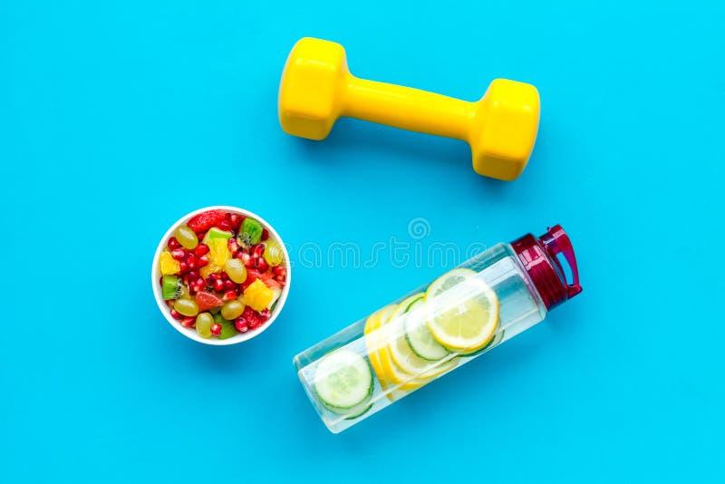 Здоровый образ жизни, здоровые привычки Вода вытрезвителя, фруктовый салат, гантели оборудования спорта на голубом взгляде сверху стоковые фотографии rf