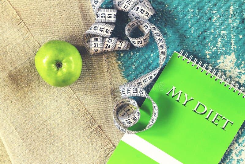 Здоровый образ жизни, тетрадь, яблоко, измеряя лента, диета МОЙ УМРИТЕ стоковая фотография