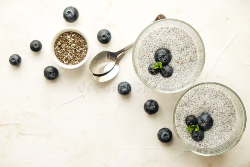 Здоровый питательный десерт superfood vegan с органическими ягодами и семенами chia с различными вариантами сервировки на деревян стоковое фото