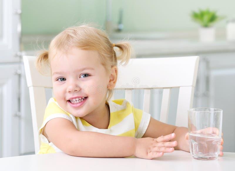 Здоровый портрет девушки маленького ребенка со стеклом воды стоковые изображения rf
