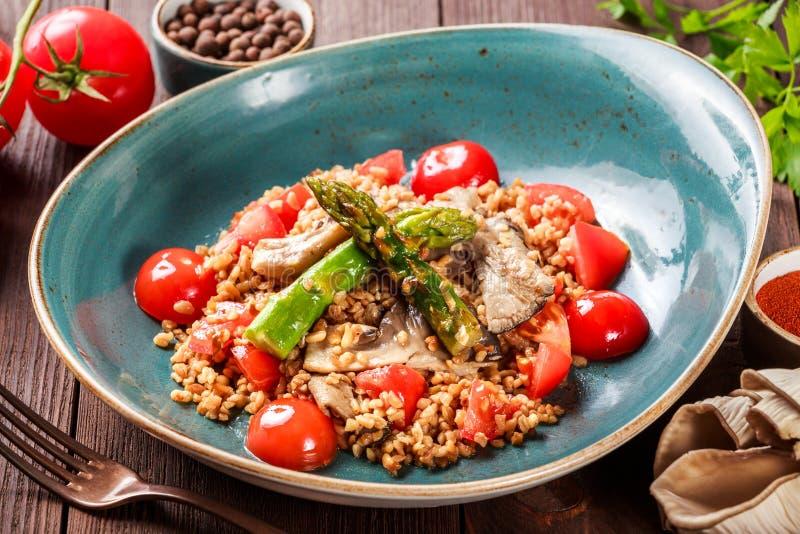 Здоровый салат каши ячменя с спаржей, томатами и грибами на плите стоковые изображения