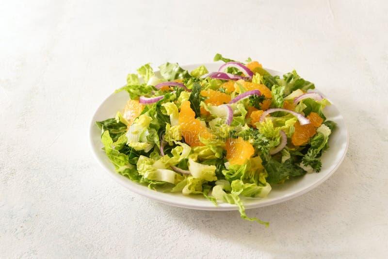 Здоровый салат от tangerines и салата с красными луками на белой плите, яркой предпосылкой с большим космосом экземпляра стоковые фотографии rf