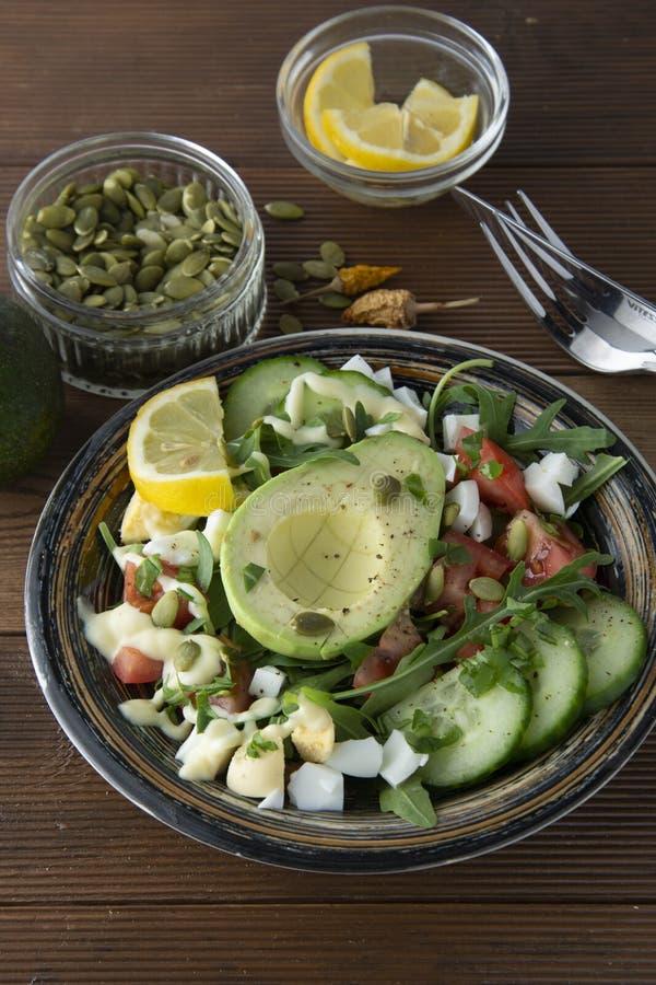 Здоровый салат свежих овощей - томатов, авокадоа, arugula, яйца, шпината Плоское положение Взгляд сверху стоковое фото rf