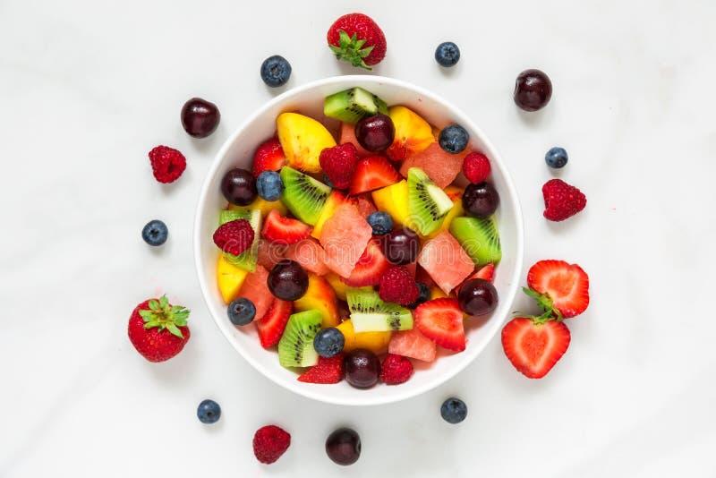 Здоровый салат свежих фруктов и ягоды в шаре на белой мраморной предпосылке еда здоровая стоковое изображение