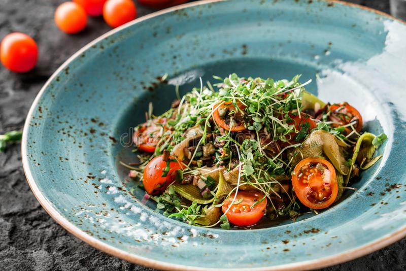 Здоровый салат vegan с оливками, луками, цукини, томатами вишни, ростками в керамической плите над темной предпосылкой Здоровая е стоковая фотография rf
