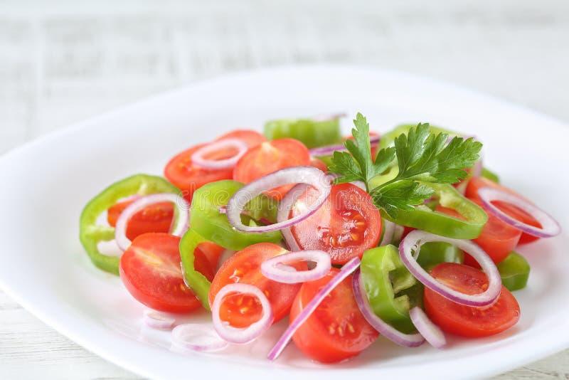 Здоровый, свежий и очень вкусный vegetable салат с томатами вишни, кольца красного лука, кольца зеленого перца, петрушка и оливко стоковая фотография