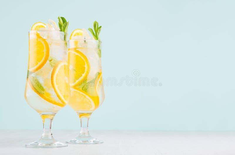 Здоровый свежий коктейль апельсинов с отрезанным плодом, кубами льда, зеленой мятой на элегантной мягкой голубой стене цвета и бе стоковое фото