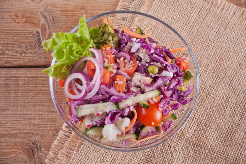 Здоровый свежий салат в шаре с красной капустой, томатом, квиноа, зеленым салатом и редиской на деревянном столе r стоковое изображение rf