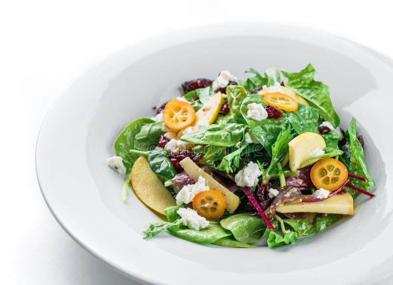 Здоровый свежий салат с зелеными цветами смешивания, яблоком, плавленым сыром, клюквой, соусом и съестными цветками в плите на из стоковые фотографии rf