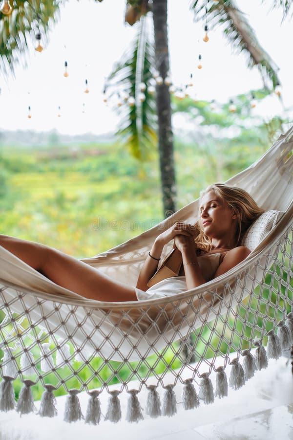 Здоровый сон на открытом воздухе на гамаке ослабляя сексуальная женщина стоковое фото