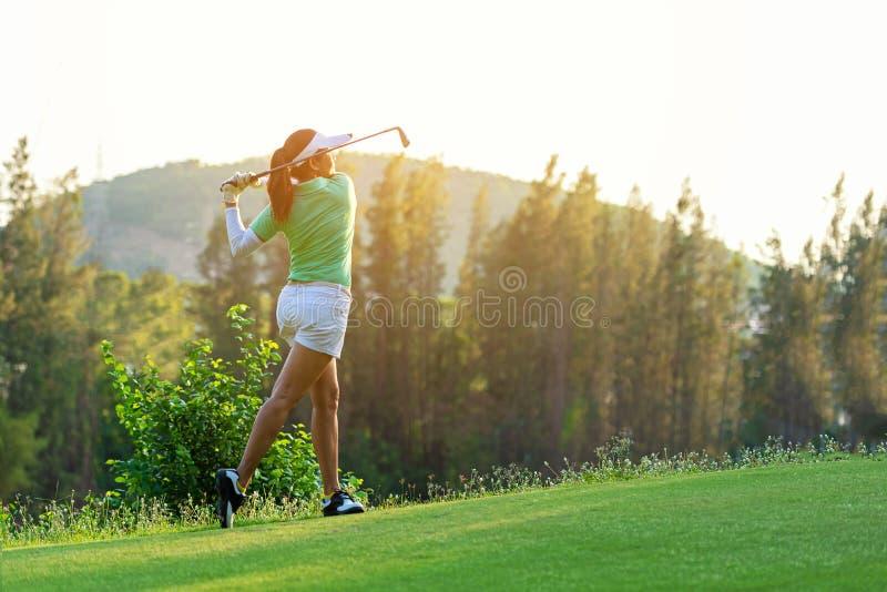Здоровый спорт Азиатский Sporty игрок игрока в гольф женщины делая тройник качания гольфа на зеленом выравниваясь времени, она пр стоковые изображения rf