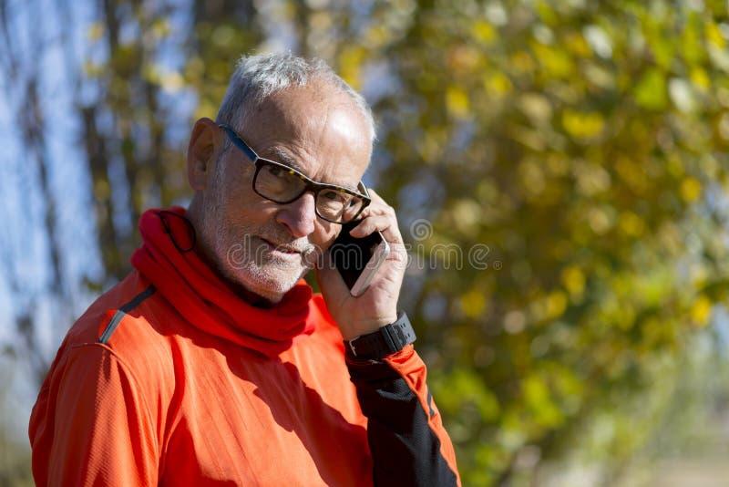 Здоровый старший человек на парке телефона внешнем стоковые фотографии rf