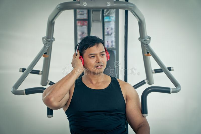 Здоровый человек фитнеса используя слушать музыку через наушники и усмехаться после разминки в спортзале стоковая фотография