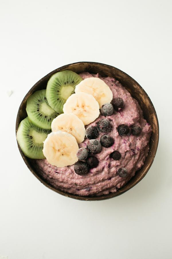 Здоровый smoothie с плодами, плитой сделанной из раковины кокоса и деревянной ложкой стоковое фото rf