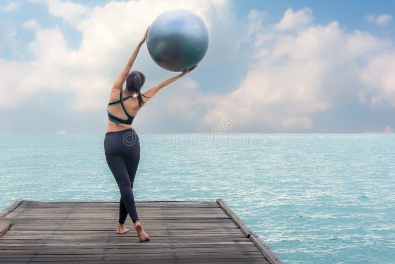 Здоровым практиковать шарика йоги женщины сбалансированный образом жизни размышляет и энергия на мосте в утре seashore стоковое фото