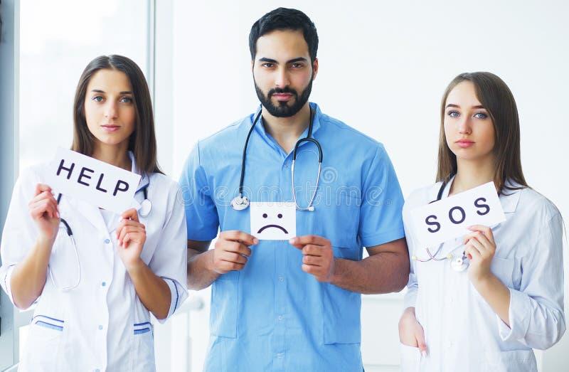 здоровье внимательности рукояток изолировало запаздывания Медицинская бригада держа надписи для помощи на h стоковое изображение rf